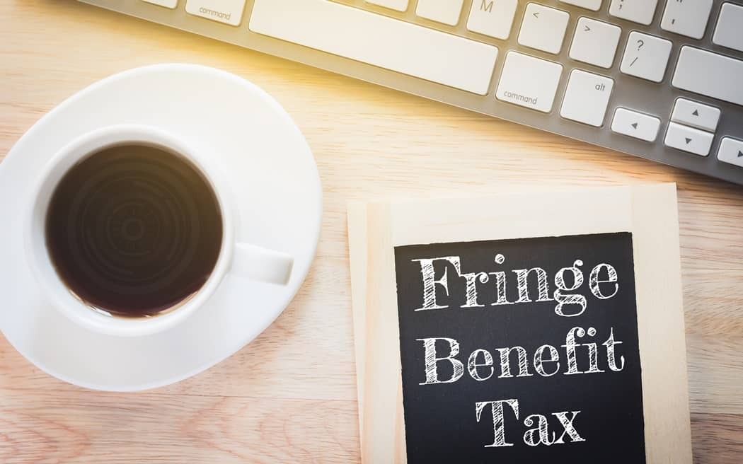 Concept Fringe Benefit Tax message on wood boards. A keyboard and a glass coffee table.Vintage tone.